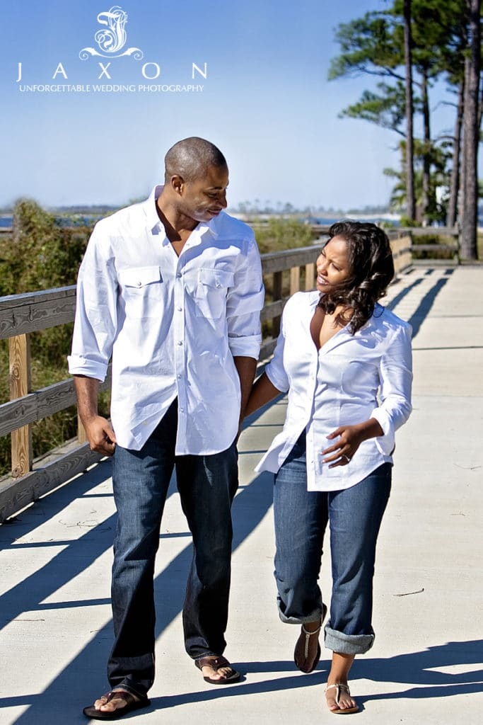 Couple in white shirts and jeans on boardwalk
