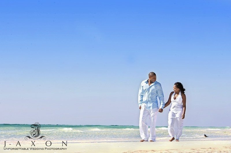 Couple walks on the beach in bright sunlight