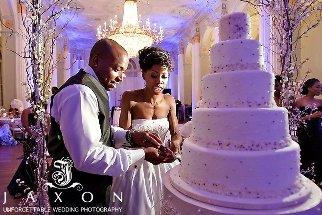 Bride and groom cutting wedding five tiered wedding cake in the georgian ballroom | Biltmore Ballrooms Real Wedding