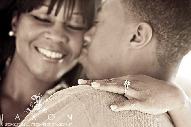 photo of engagement ring on grooms shoulder couple smiling in the background
