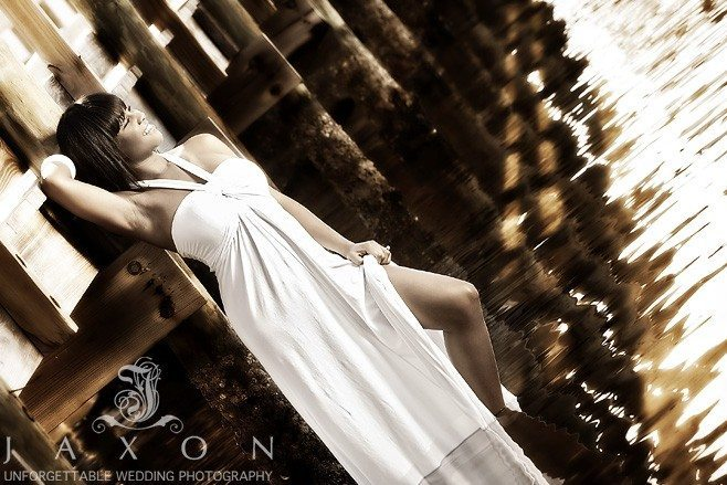Sepia portrait of young woman leaning against a pier in a halter style white sundress in a suggestive pose