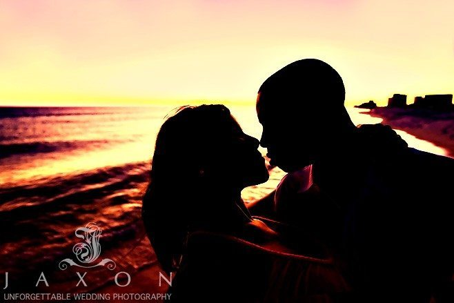 Silhouetted Sunset engagement photo of couple kissing