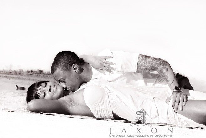 B&W portrait of couple in white laying and kissing on the beach