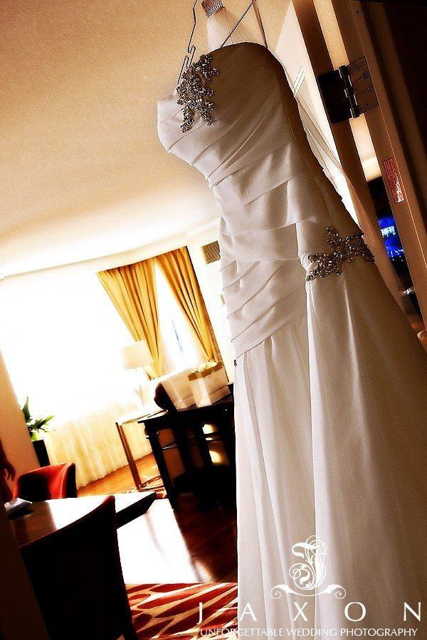 Brides The bride's silver bejeweled wedding dress hangs on the closet door in suite for her Ritz Carlton Atlanta wedding