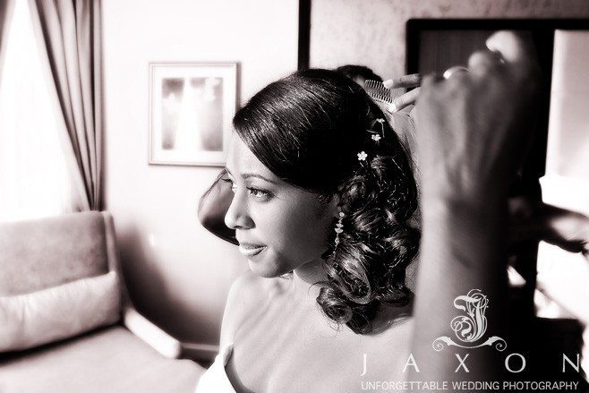 wedding hair styles | Hair stylist applies finishing touches before wedding ceremony