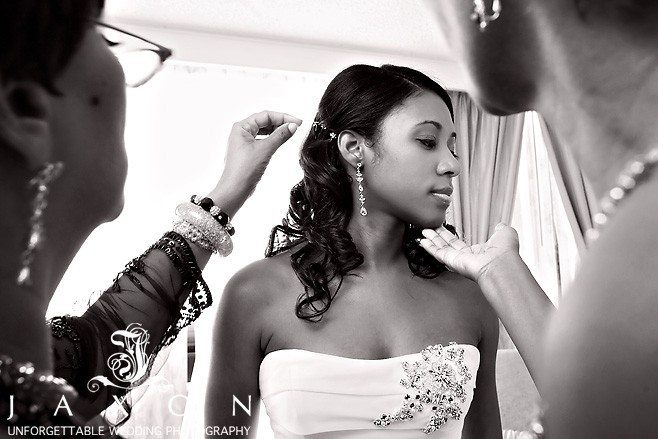 Bride and party applies finishing touches to the brides hair for her wedding at the Ritz