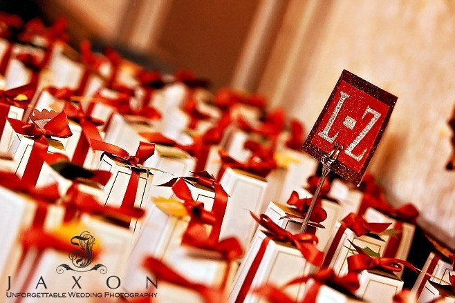 Beautiful red ribbon wrapped white and gold boxed wedding guests favors
