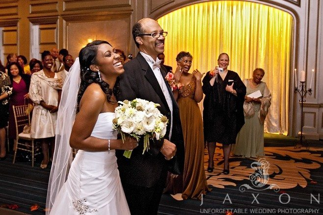 father escorts his daughter into ballroom for her wedding ceremony