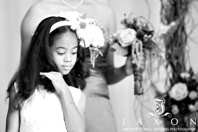 documentary wedding photography, photographer image captures the flower girl totally unaware as she plays with her hair during the ceremony