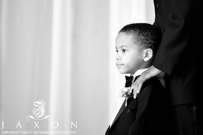 B&W picture of attentive Ring Bearer focused on the proceeding during wedding ceremony