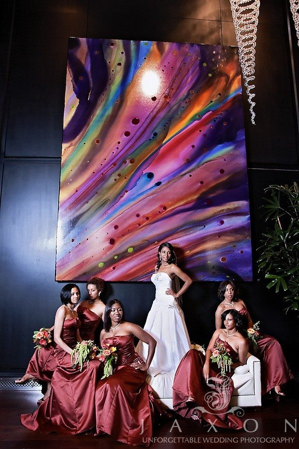 Glamorous bridal party sits around the bride standing on backless sofa in the Peachtree Street Foyer Entrance too the Ritz Carlton Atlanta