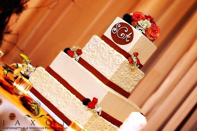Four tiered square wedding cake decorated with red ribbon, roses and monogrammed with couples initials
