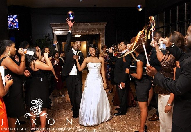 Jubilant couple exits their wedding reception as well wishers cheers blow bubbles, wave streamers