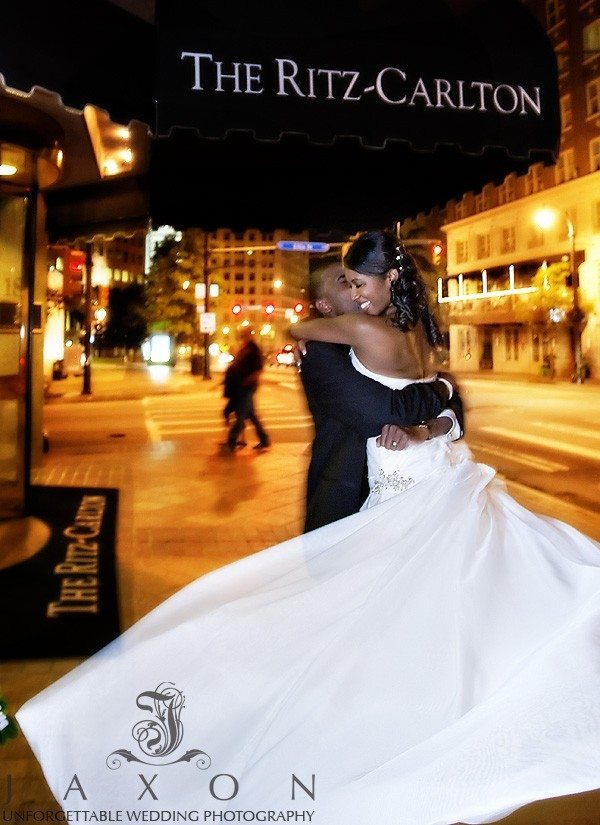 in this night time photo groom lifts and twirls his new bride on Peechtree st in front of downtown Atlanta's Ritz Carlton Hotel