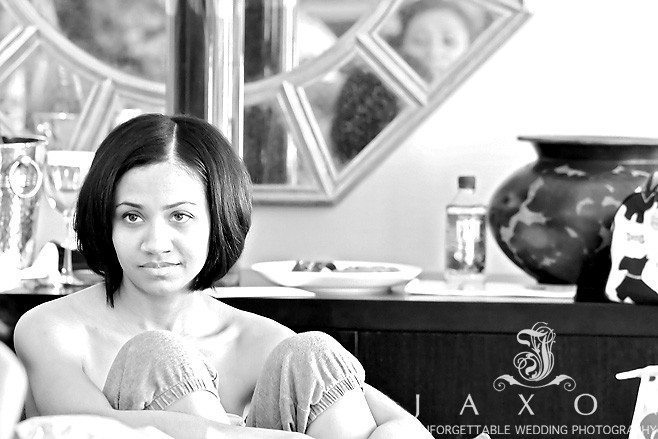 in this sepia picture Bridesmaid looks on intently as wedding party prepares for wedding ceremony