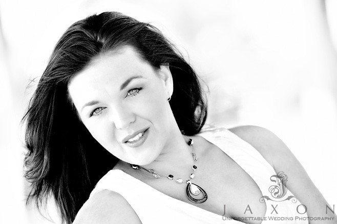 B&W portrait of female in a white dress hear long hair blowing in the breeze