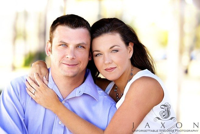 Portrait of couple on beach her arms wrapped around his shoulders