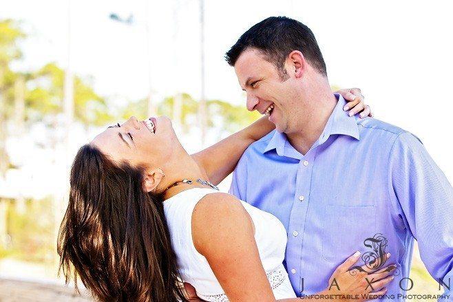 Couple embrace on the beach and enjoy a laugh   Sandestin Beach Engagement