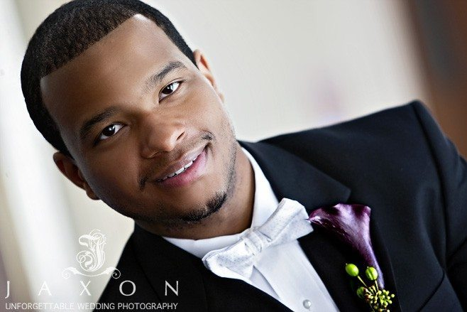 Portrait of the groom in his black tux with white shirt and bow tie, sporting a purple calla lily boutonniere