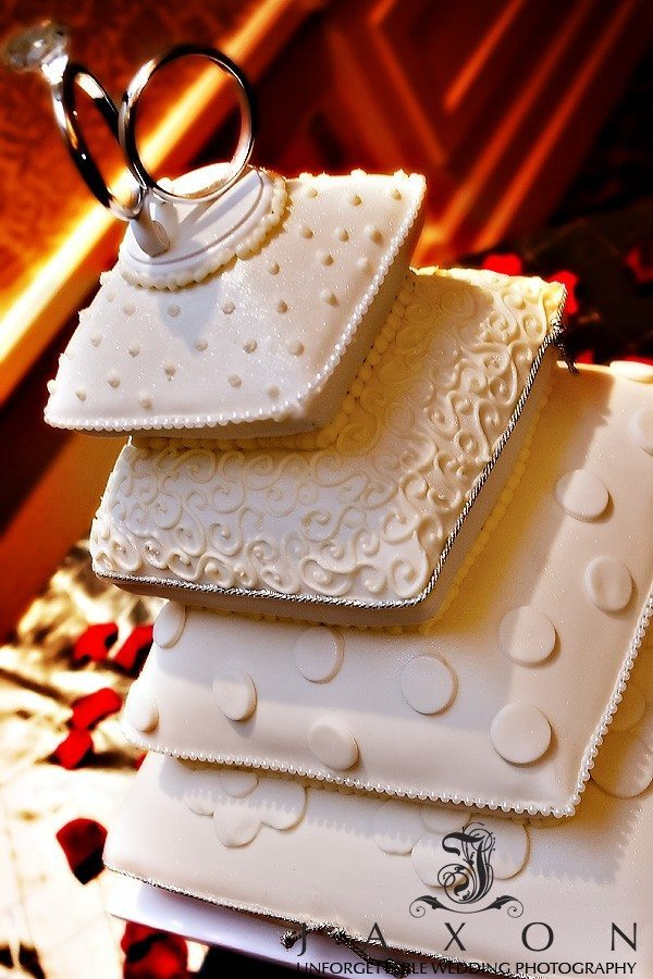 Four Tiered Pillow Cushioned Wedding Cake topped with two wedding bands