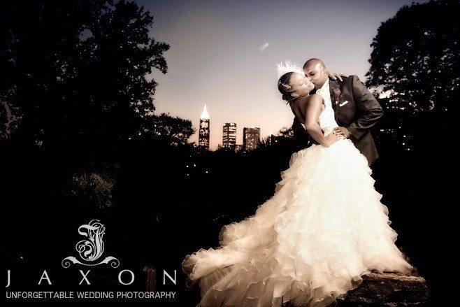 A dramatic sepia photograph of couple on a column in wedding attire with the city of Atlanta Skyline as a backdrop | Atlanta Botanical Gardens
