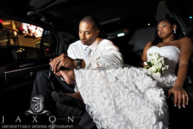 Groom gives his bride a foot rub in the limo