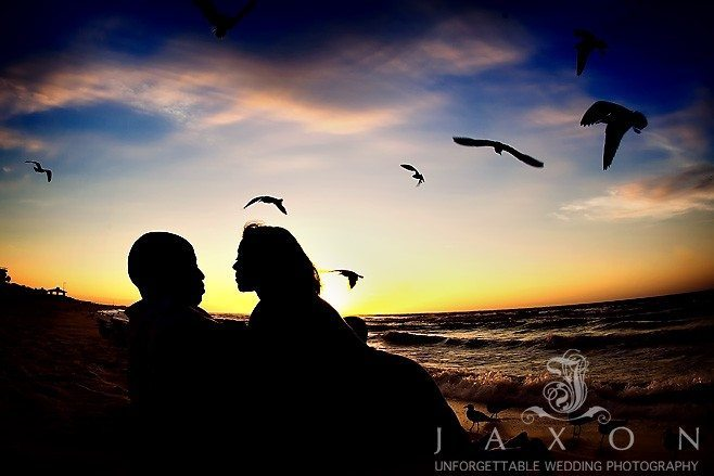 Couple Silhouetted against a dramatic late evening sky on the beach with sea gulls flying overhead