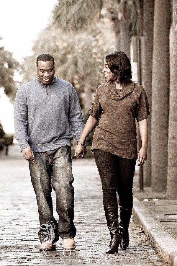 Couple walks hand in hand along Charleston's cobblestone streets of Charleston