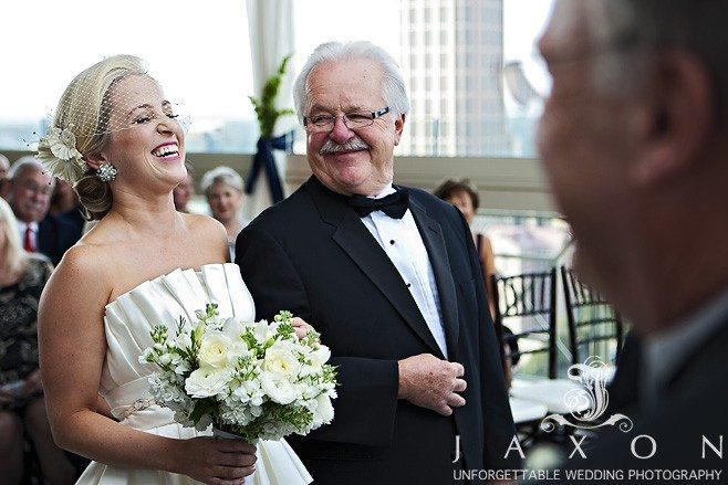 Bride laughs out loud during wedding ceremony as dad an minister smiles | Peachtree Club Roof top Weddings