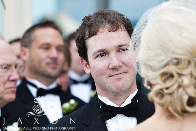 Grooms look on intently, | Peachtree Club Roof-top Weddings