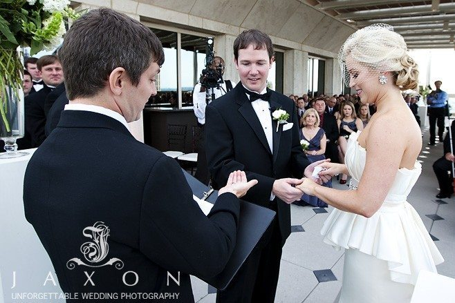 Ring ceremony Grooms look on intently, | Peachtree Club Rooftop Weddings