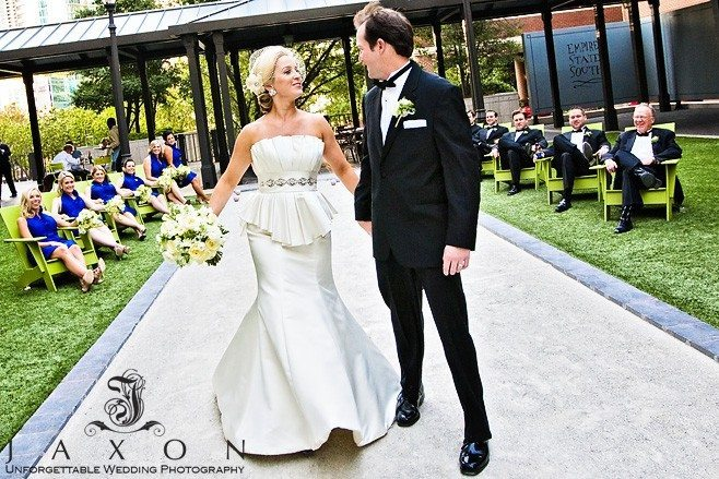 Bride and groom walks on the bocce ball court while their wedding party is seated on green chairs in the background in the courtyard ay 999 Peachtree. | Peachtree Club Roof top Weddings
