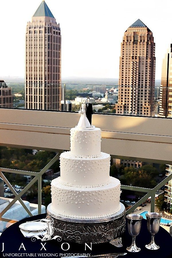 Three tiered round white wedding cake on the rooftop at The Peachtree Club Wedding photos