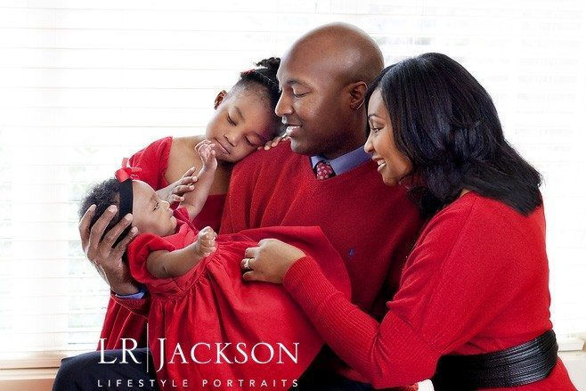 Family of 4 in red celebrates the newborn baby girl at Christmas