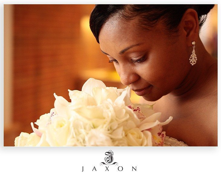 Bride smelling her bouquet of white roses