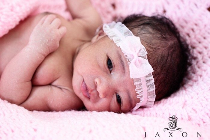 New born baby girl in pink blanket with pink bow