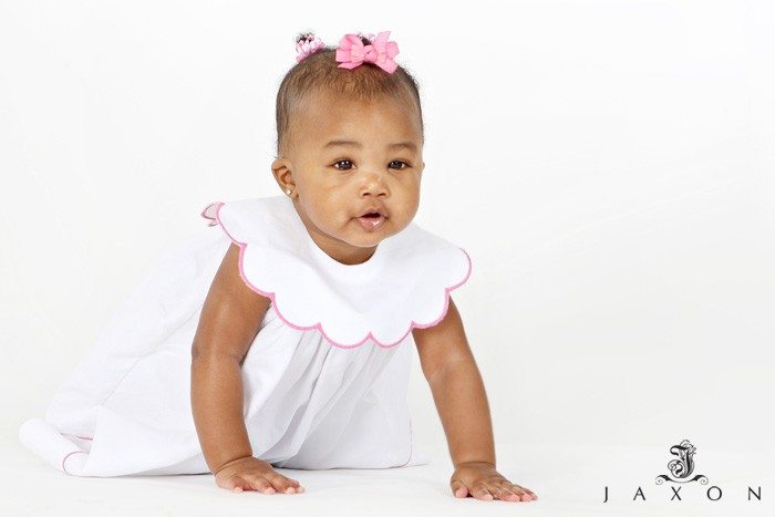 One yr old baby girl in white dress trimmed with pink and pink bows in her hair. Crawling against a white backdrop.