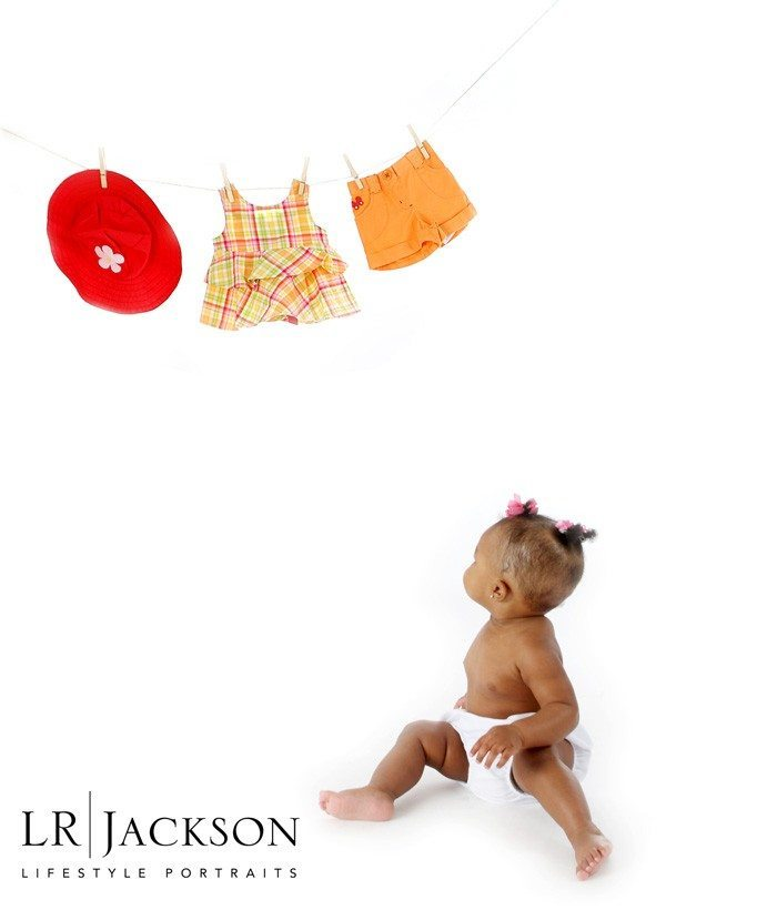 Portrait of baby in studio looking at her clothing on a clothes line