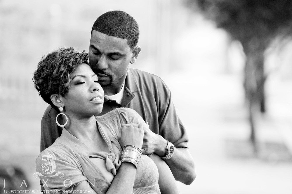 African American couple wrapped in each others arms during engagement session