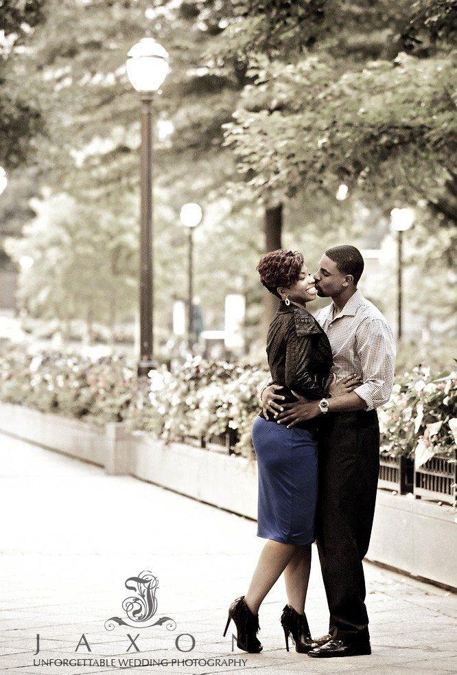 Couple embrace along peachtree st next to woodruff park in ATlanta