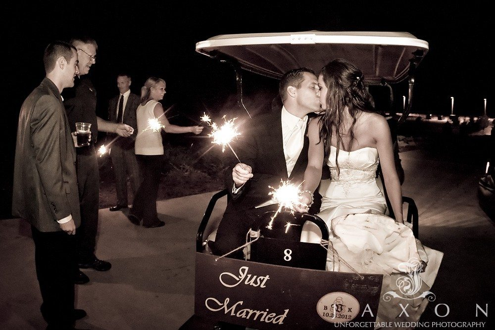Couple kisses as they leave the wedding reception on the back of a golf car, PineIsle Pointe | Lake Lanier Wedding