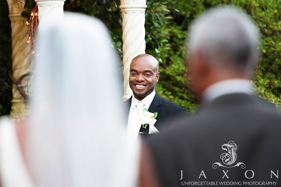 Groom smiles broadly in the image of him framed by his wife to be and her escort | atrium norcross wedding
