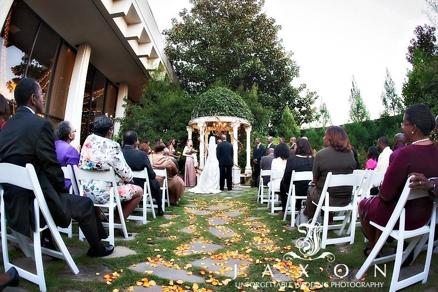 Beautiful wide angle photograph of the garden ceremony in progress with yellow rose petals strewn amongst the flagstone walkway | atrium norcross wedding