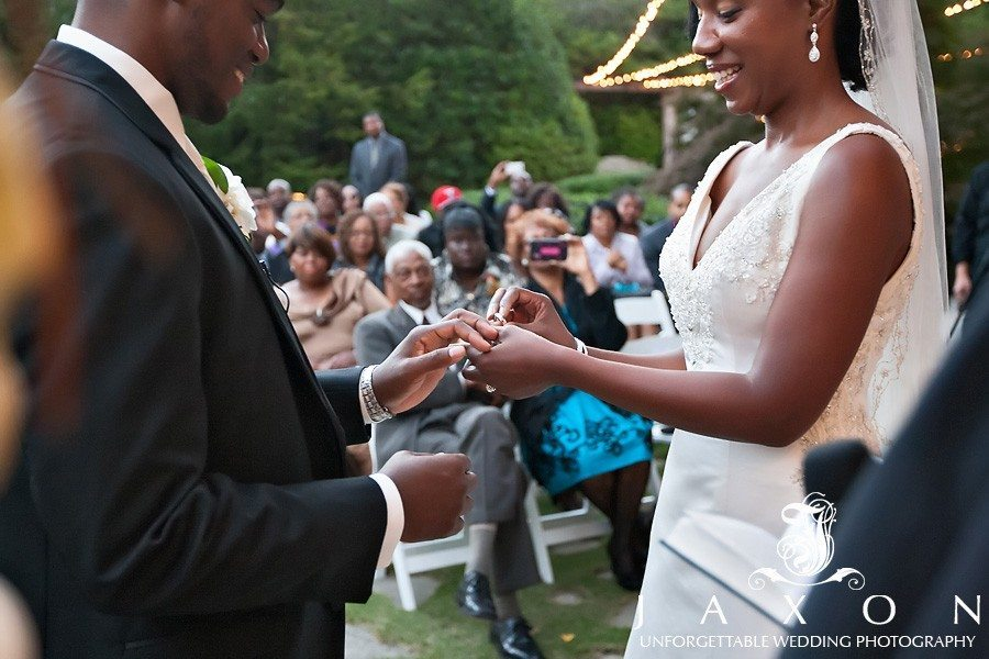 Couple exchange wedding bands against a backdrop of the guests in the garden| atrium norcross wedding