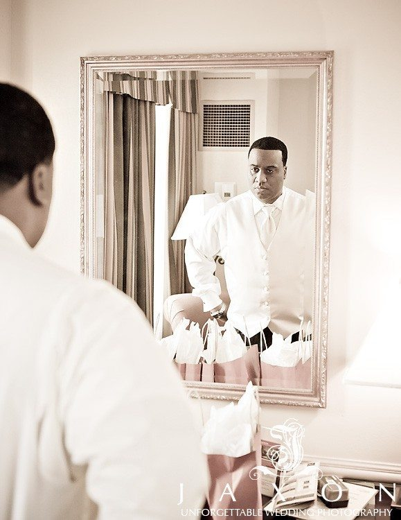 Groom makes final inspection in the mirror before wedding