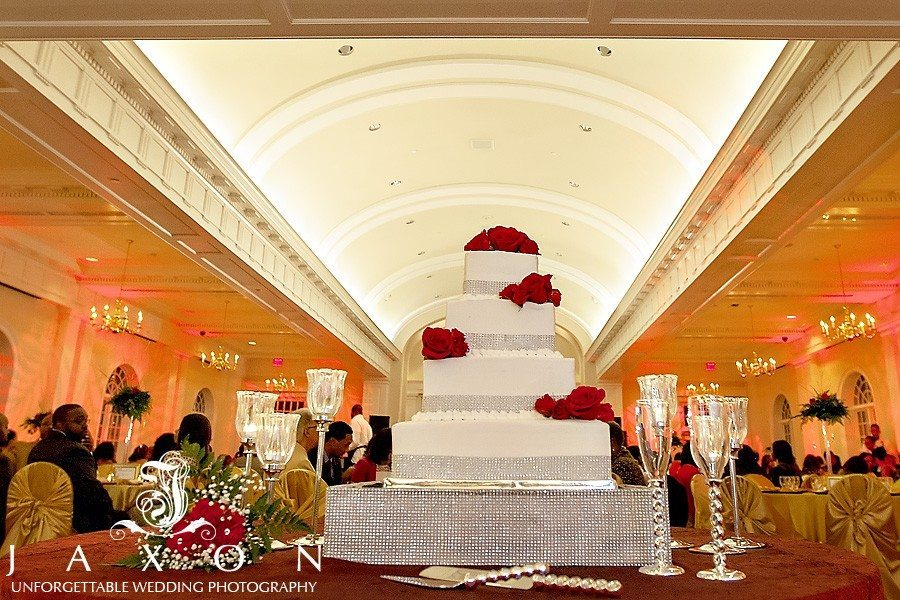 Four tiered square wedding cake decorated with silver ribbon and red roses