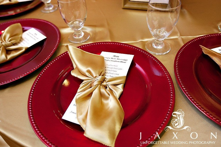Wedding menu wrapped in a gold napkin on a red charger