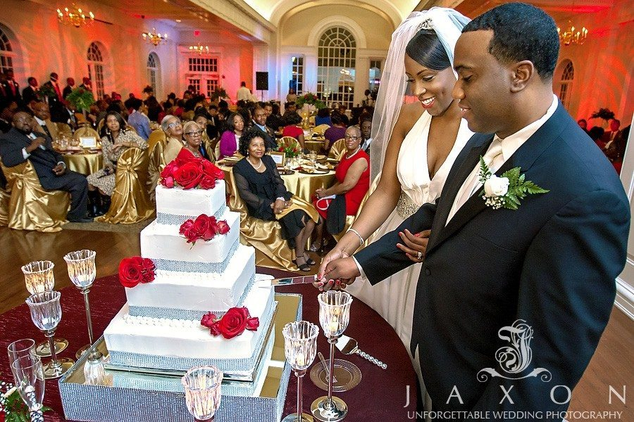 Bride and groom cuts Four tier square wedding cake as guests looks on | River Room wedding Augusta