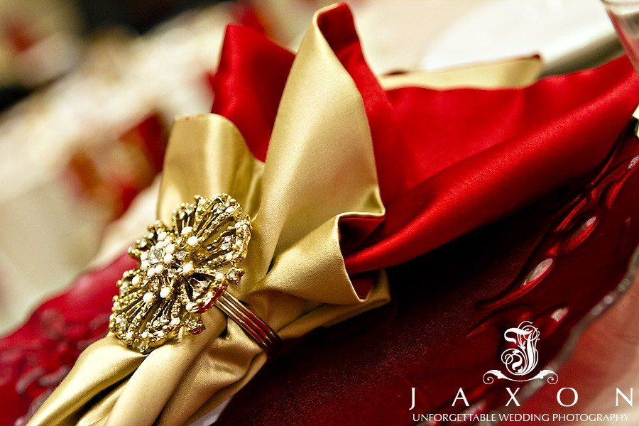 Red and gold napkin with gold napkin holder on clear charger | marriott gateway weddings