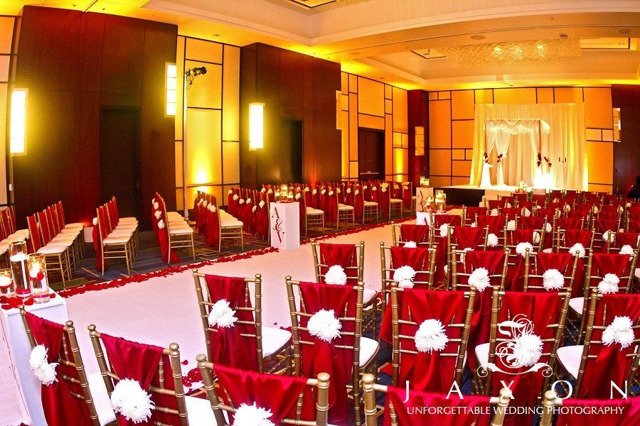 Ballroom with a color scheme of red and white, gold Chiavari chairs covered wit red fabric with a white flower tieback | Marriott Gateway Atlanta